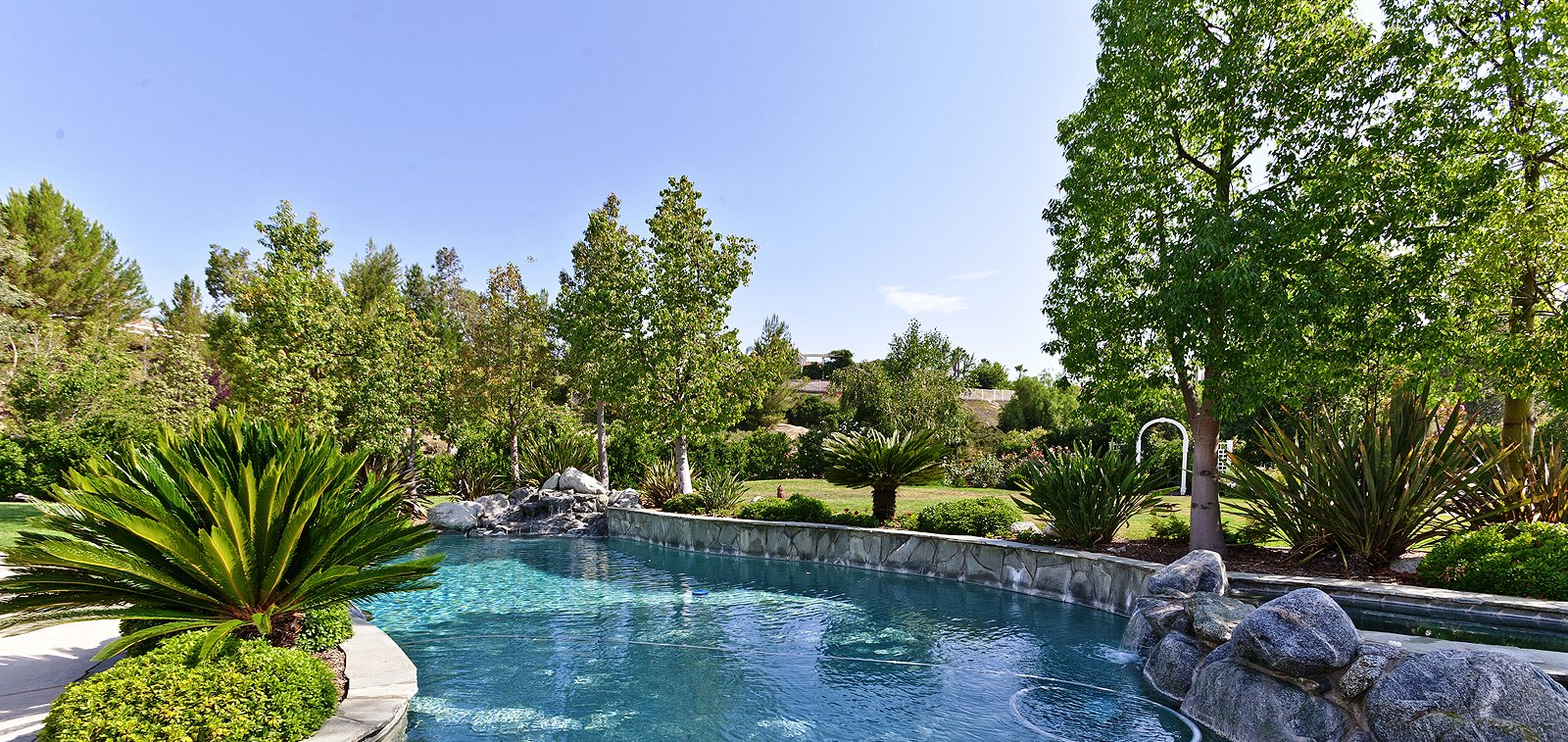 THE HENSLEY GROUP REAL ESTATE - beautiful swimming pool amidst lush greens