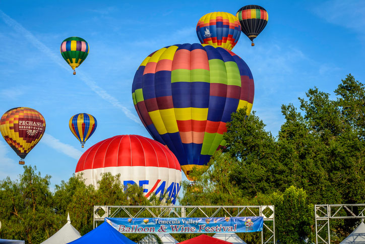 Colorful balloons ascend into the morning sky